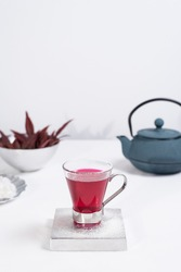 A transparent cup of red fruit tea with blue iron teapot on a white table and a light gray background