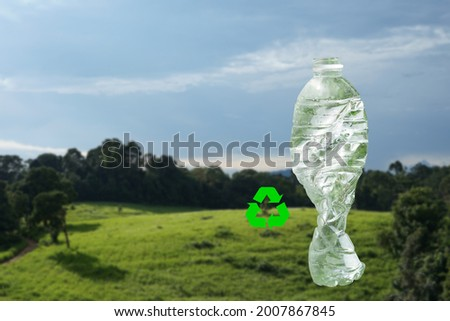 a transparent empty plastic bottle is squeezed and recycling symbol, background blurred nature, concept of waste sorting, recycled plastic waste campaign to reduce global warming Foto stock ©