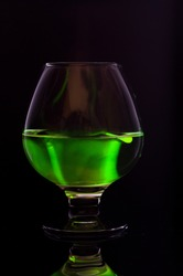 A transparent glass goblet with a green substance. A bright green substance in a glass.