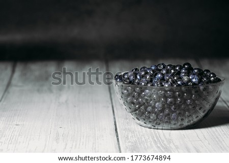 A transparent glass plate is filled with ripe tasty blueberries on a dark background. Copy space. Place for text