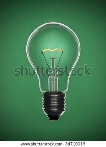 A transparent light bulb over a green background. Tungsten glowing filament.