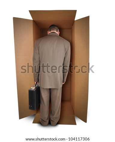 A trapped business man is walking into a brown box to represent a challenge or unemployment on a white background. The employee is wearing a suit.