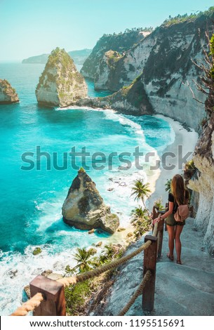 A travel girl with backpack and in shorts on the ocean, cliffs and tropical beach background. Nusa Penida, Indonesia. Female silhouette