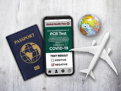 A travel theme with generic passport and a smartphone app that shows Negative PCR test result for Covid-19.