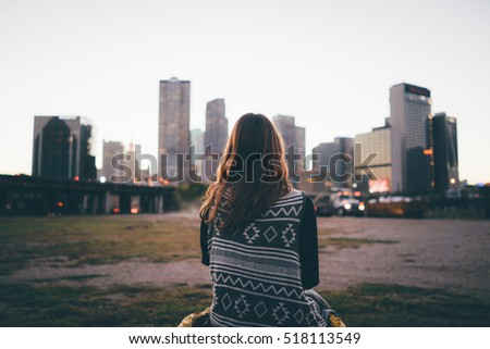 A traveler brunette girl is looking at the city skyline during in the evening.