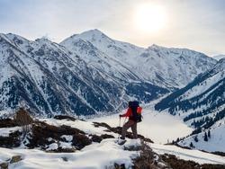 A traveler meets dawn on a mountain lake in winter. Morning winter mountain landscape. Big Almaty Lake. Kazakhstan