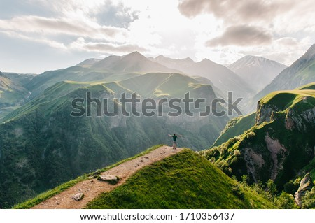 A traveler on the edge of a cliff with a spectacular view behind him. Amazing view of the Devil's Valley in the mountains of the Caucasus. Georgian military road in Georgia, beautiful mountains.