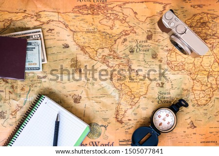 A traveler plans his trip around the world on an ancient  old map, while taking notes to get inspired. #1505077841