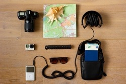 A traveler's kit.  Photo and action cameras, music player, sunglasses, headphones, document bag with passport and money inside, pocket knife, paper map and a sea shell. Wooden background. Top view.