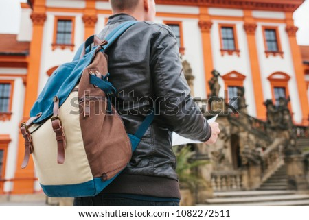 A traveler with a backpack looks at the map next to the castle in the Czech Republic. Tourism and sightseeing. A tourist in a beautiful tourist place. #1082272511