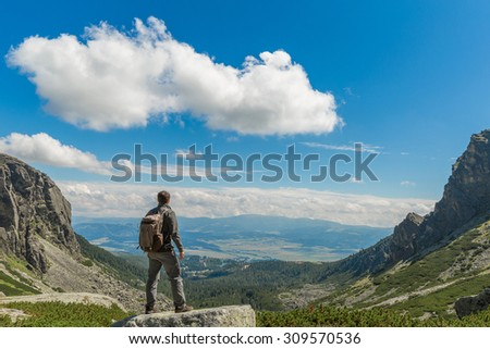 A traveler with a backpack standing on a mountain peak.