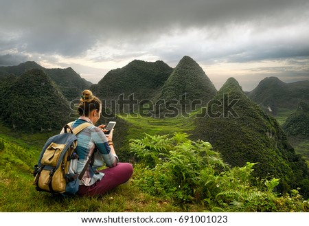 A traveler with a smartphone is exploring a picturesque karst mountain plateau in the North of Vietnam.Traveling and exploration along mountains, freedom and active lifestyle concept.