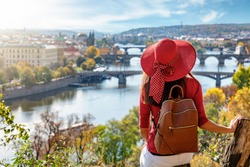 A traveler woman with red hat enjoys the elevated view over the city of Prague, Czech Republic, on a sunny autumn day
