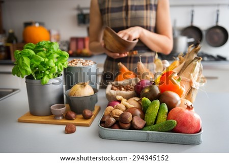 A tray full of Autumn fruits, nuts, and vegetables sits on a kitchen counter. Next to the tray, a wooden cutting board featuring a fresh basil plant and onion promise a delicious meal ahead. #294345152