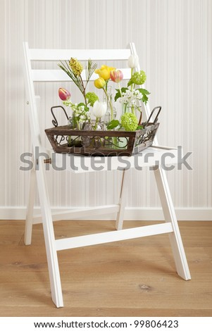 A tray full of different flowers on a folding chair