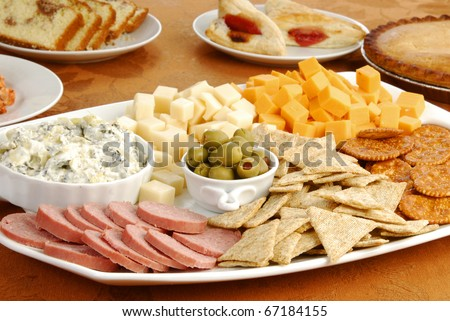 A tray of cheese, crackers and dips on a table with baked party foods