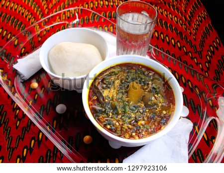 A tray of Nigerian food, fufu with okra soup containing cow skin meat (Nigerian Kpomo) and dried fish on a colorful red table cloth