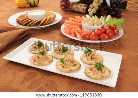 A tray of wheat crackers with lobster dill spread and a vegetable platter in the background