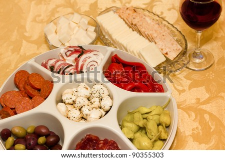 A tray with an assortment of Italian antipasto consisting of cheese, olives, peppers and Italian meats