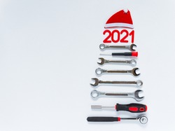 A tree made of construction tools with a New Year's red hat on a white background. New Year concept 2021 for a car workshop. Unusual Christmas tree