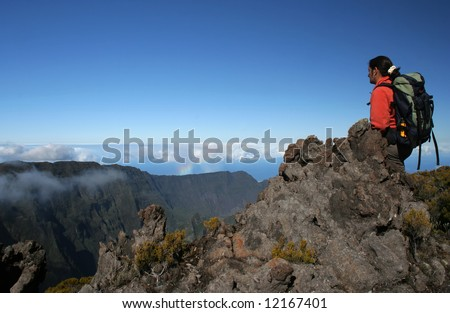A trekker on top of the Mountain, above clouds (Reunion Island/Africa).