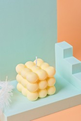 A trendy soy cube bubble candle on a light blue podium
