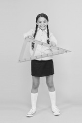 A triangle has three sides and three angles. Adorable happy schoolchild holding triangle on yellow background. Cute girl smiling with geometric triangle for geometry lesson. Lesson in triangle.