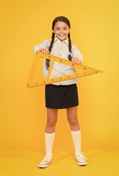 A triangle has three sides and three angles. Adorable happy schoolchild holding triangle on yellow background. Cute girl smiling with geometric triangle for geometry lesson. Lesson in triangle