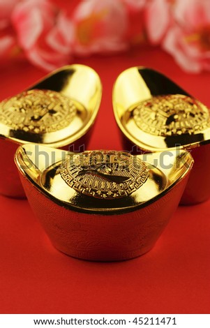 A trio of chinese gold ingots on a red background with some cherry blossoms in the background