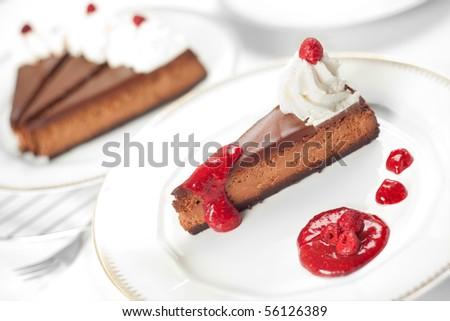 A triple chocolate cheesecake with raspberry sauce and whipped cream. Shallow depth of field on the slice