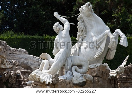A triton (creature who is half-man and half-fish) statue in the Neptune Fountain at the Schonbrunn Palace, Vienna, Austria