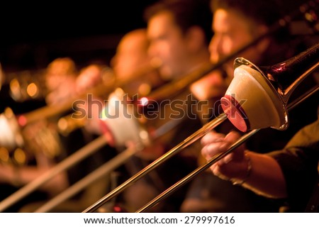 A trombone section playing together in a traditional big band jazz ensemble. Selective focus on the foreground trombone.