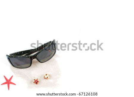 A tropical Christmas border with a red star fish in the corner,a pair of sunglasses with a reflection of a Caribbean beach and a couple of ornamental bells on some white beach sand.