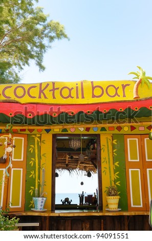 A tropical cocktail bar, with the sea behind.