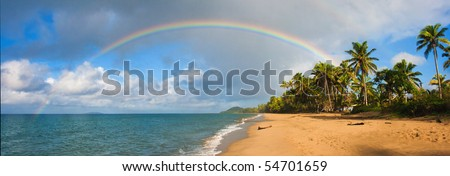 A Tropical Pacific oceanscape with palmtrees, rainbow, clouds - stock photo