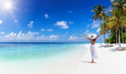 A tropical travel concept banner with copy space showing a woman in white dress walking down a paradise beach with palm trees and turquoise sea