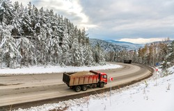 A truck is driving on a winter forest road. Winter forest road truck. Truck on snowy winter road. Winter snowy truck trip