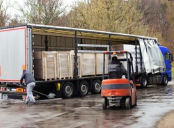 A truck is loaded with goods wrapped on pallets, a trucker is making a move while lowering the side board and the forklift is moving while approaching the goods to unload it while raining.