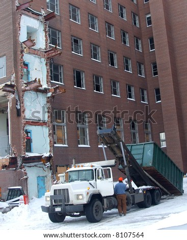 A truck picks up a refuse bin at a demolition site in winter. #8107564