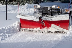 a truck with a snow blade clears snow after a storn  in a residential area in Michigan USA