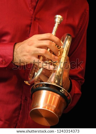 A trumpeter holds his instrument, a pocket trumpet with mute. Black background.