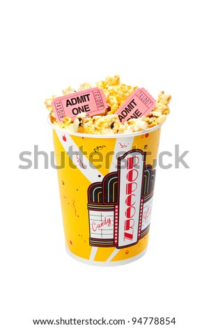 A tub of popcorn with movie tickets on top.