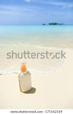 a tube of sunblock on the sandy beach, against the turquoise sea