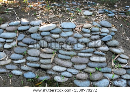 A tubercle with smooth edges, the wall of which is lined with large pebbles. Large pebbles to strengthen the earth in the botanical garden. Strengthening slopes.