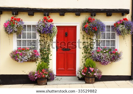 A Tudor cottage, with a beam and bright red door, has colorful hanging baskets and window boxes.
