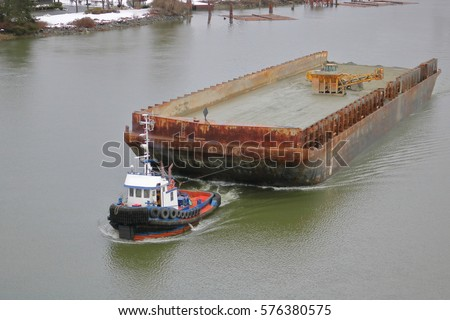 A tug boat hauls a large, empty barge down river/Tug Boat and Large Empty Barge/A tug boat hauls a large, empty barge down river.
