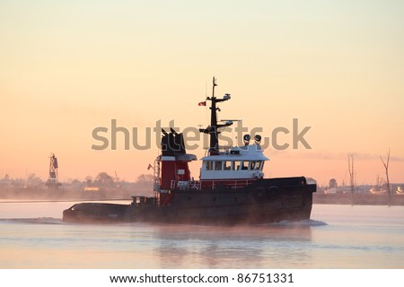 A tug boat motors down the Fraser River through the early morning mist.