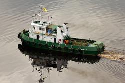 A tug boat pulling a pontoon on the river Sunga Belait, Brunei