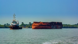 A tug boat pulls a large cargo barge transporting bauxite ore for offshote transshipment in Kamsar, Guinea.