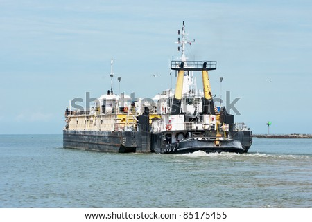 A tug boat pushes a cement barge out of the Cuyahoga River and into Lake Erie at Cleveland, Ohio